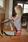 "Cutting up paper to make ""money"" -- notice how she places everything in an ordered line"