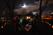 Christmas Even full moon rising over carolers and luminarias